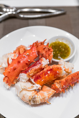 Alaskan king crab and seafood on white dish with seafood sauce