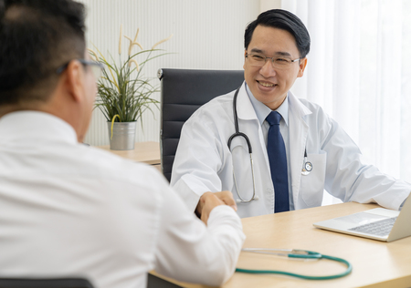 Portrait of Young adult Doctor with Patient in examination room medical office.