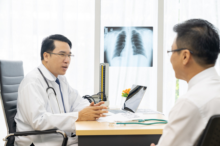 Professional doctor explain about x-ray result to patient in medical office hospital