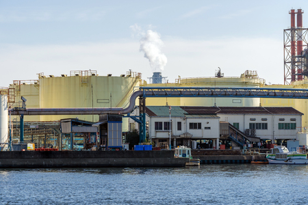 Fuel oil Storage Tank with smoke from boiler in background in Kawasaki Japan
