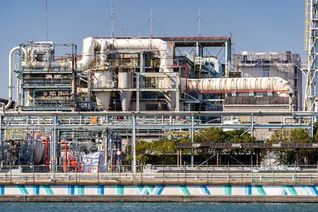 Chemische fabrieksfabriek met gasopslag en structuur van pijpleiding met rook uit schoorsteen in Kawasaki-stad bij Tokio, Japan