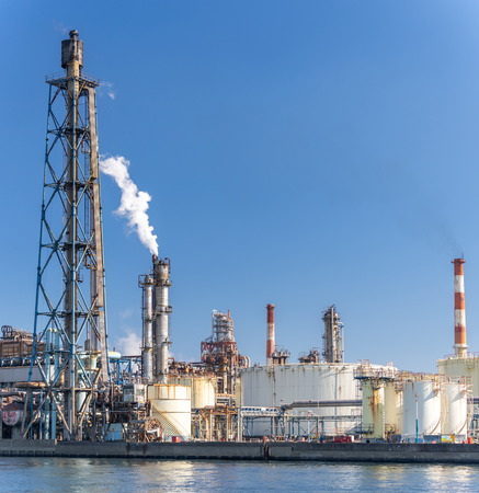 Chemische fabrieksfabriek met gasopslag en structuur van pijpleiding met rook uit schoorsteen in Kawasaki-stad bij Tokio, Japan Redactioneel