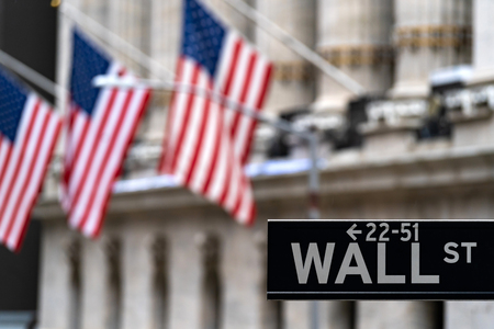 Wall street sign with New York Stock Exchange background New York City, New York, USA.