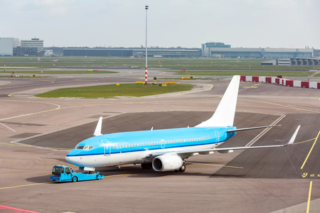 Blue Airplane waiting on taxiway ready to takeoff