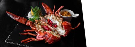 Grilled boston lobster serve with butter chilli sauce with lemon and salt. Panoramic crop designed for using as web banner