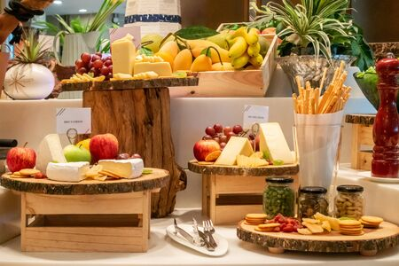 Variety of cheese with variety of fruit and cracker on wooden plate in buffet line