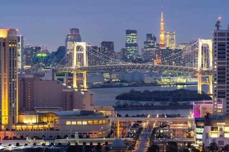 Aerial view of Tokyo Sunset with Tokyo tower and Rainbow bridge with Tokyo cityscape in background from Odaiba Japan.