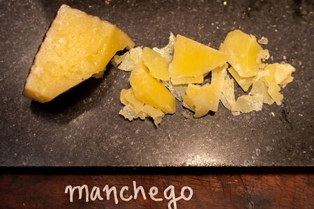 manchego cheese on black stone plate in buffet line