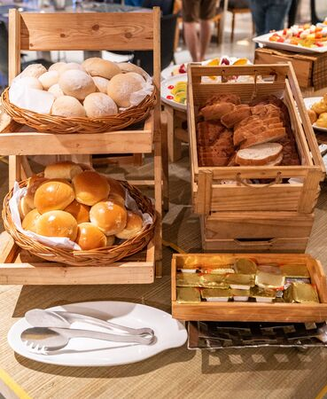 variety of bakery bread and rolls station in buffet line