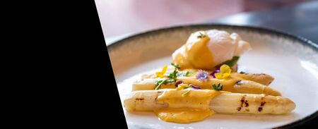 Gourmet grilled white asparagus with poached egg serve with hollandaise savory sauce decorate with edible colorful flowers designed for using as web banner