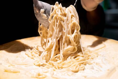 Chef cooking pasta in cheese bowl Imagens