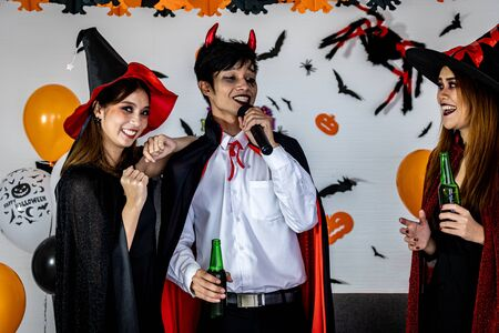 Group of young adult and teenager people celebrating a Halloween party carnival Festival in Halloween costumes drinking alcohol beer singing a song and dancing.