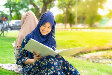 Teenager Young Adult Asian Thai Muslim university college student reading book together using for education concept Banco de Imagens