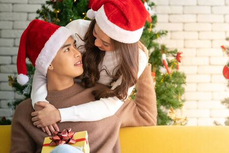 Young asian adult teenager couple hugging and  celebrateing christmas holiday together in living room with christmas tree decoration.