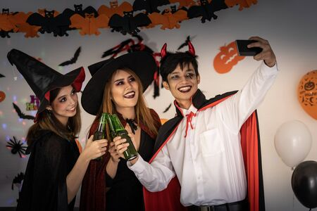 Group of young adult and teenager people celebrating a Halloween party carnival Festival in Halloween costumes drinking alcohol beer and take selfie photographing.