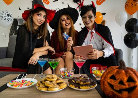 Group of young adult and teenager people celebrating a Halloween party carnival Festival in Halloween costumes and making online shopping with tablet and credit card Фото со стока