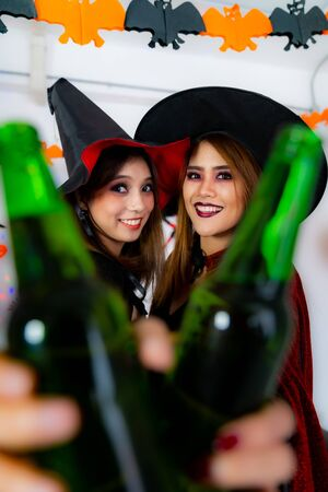 Group of young adult and teenager people celebrating a Halloween party carnival Festival in Halloween costumes drinking alcohol beer