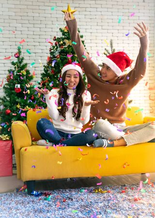 Young asian adult teenager couple celebrateing christmas holiday together in living room with christmas tree decoration. Stock fotó