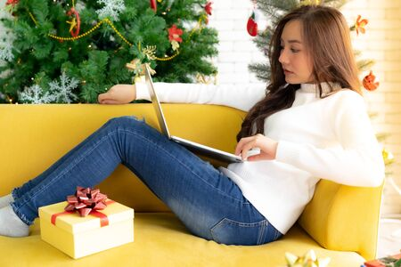 Young Adult teenager using laptop on sofa in living room for online shopping with gift box with Christmas tree in background
