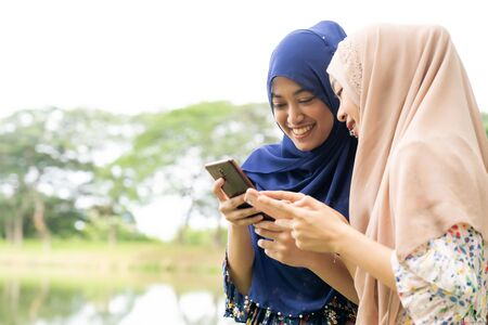 Young adult teenager Muslim Islamic Thai Asian women using smartphones and tablet in social media. Banco de Imagens