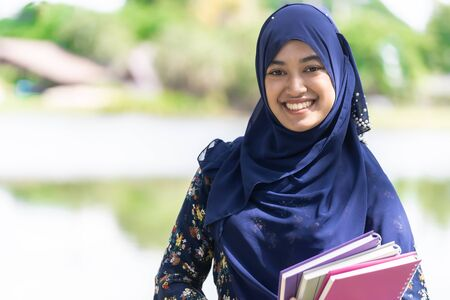 Portrait of good-looking Happy young teenager Muslim islamic asian university girl