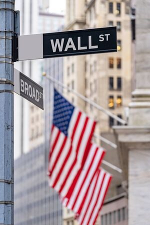 Wall street sign with New York Stock Exchange background New York City, New York, USA. Stock Photo