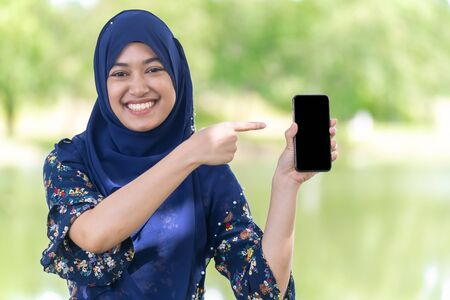 Portrait of good-looking Happy young teenager Muslim islamic asian university girl hold mobile phone Stock Photo