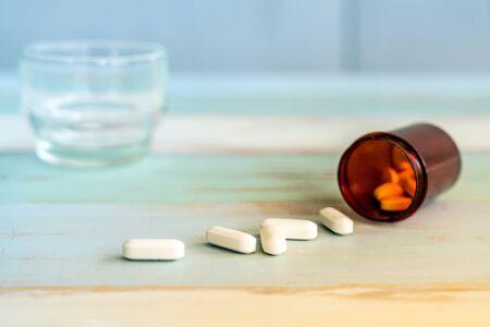 Pills medicine spilling out of pill bottle on vintage wooden background