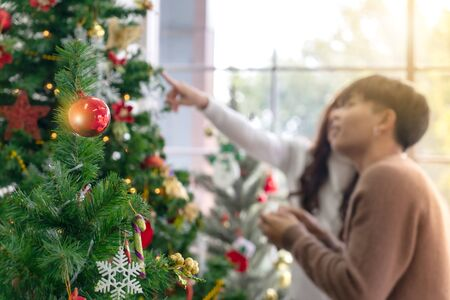 Christmas tree and ornament with background of young Teenager asian couple decorating Christmas tree together prepare for Christmas party holiday. Stock Photo