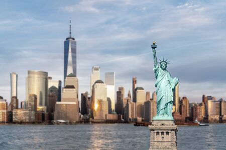 Statue of Liberty with background of New York city Manhattan skyline cityscape at sunset from New Jersey.  写真素材