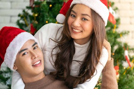 Young asian adult teenager couple hugging and  celebrateing christmas holiday together in living room with christmas tree ornament decoration. Zdjęcie Seryjne