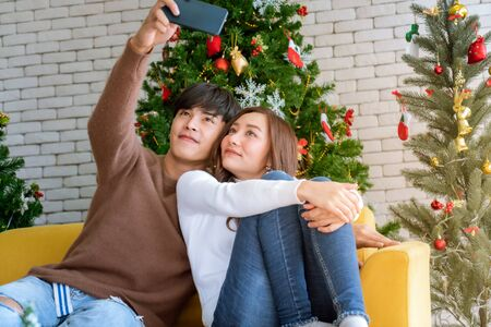 Young asian adult teenager couple take selfie photographing for celebrateing christmas holiday together in living room with christmas tree decoration. Zdjęcie Seryjne