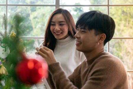 Young Teenager asian couple decorating Christmas tree together prepare for Christmas party holiday. Stok Fotoğraf