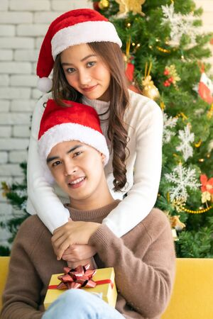 Young asian adult teenager couple holding gift present box hugging and celebrateing christmas holiday together in living room with christmas tree ornament decoration.