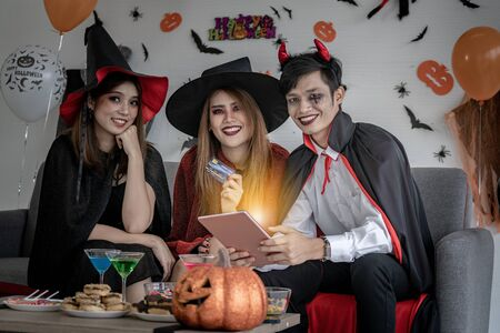 Group of young adult and teenager people celebrating a Halloween party carnival Festival in Halloween costumes and making online shopping with tablet and credit card Zdjęcie Seryjne