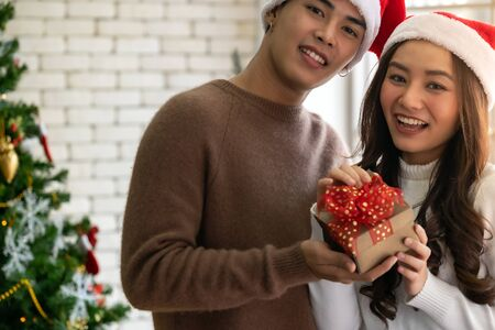 Beautiful happy asian girl receiving christmas present gift box from her boyfriend for Christmas holiday season greeting.