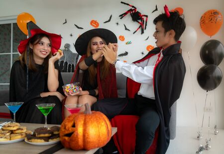 Group of young adult and teenager people celebrating a Halloween party carnival Festival in Halloween costumes with food and drink on table.
