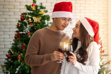 Young asian adult teenager couple celebrateing christmas holiday with wine together in living room with christmas tree decoration.