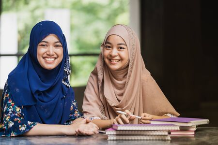 Teenager Young Adult Asian Thai Muslim university college students reading book and using digital tablet together using for education and online education concept