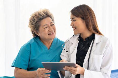 Asiatischer Vertrauensarzt mit digitaler Tablette, der gesundheitliche Bedenken mit alten älteren Patienten ausdrückt, sitzen im Rollstuhl Standard-Bild