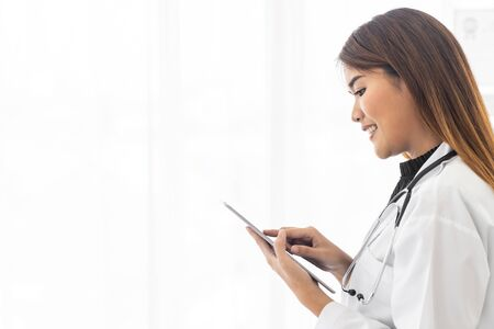Portrait confident female doctor medical professional standing and use digital tablet in examination room in hospital clinic. Positive face expression