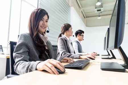Young adult friendly and confidence operator woman agent smiling with headsets working in a call center with her colleague team working as customer service and technical support workplace in background. Stock Photo