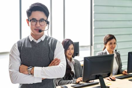Portrait of Young adult friendly and confidence operator man with headsets and his team working in a call center as customer service and technical support.