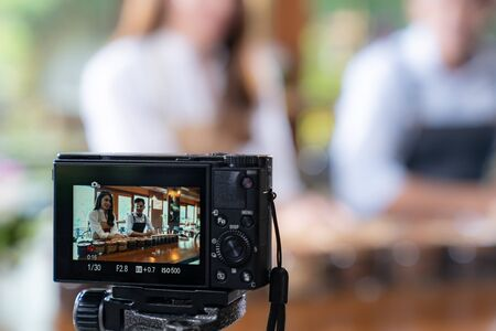 VLOG of  young adult asian owner entrepreneur review cafe coffee shop and live in social media for online marketing with camera in cafe. Using for startup of small business marketing and consumerism concept. Stock Photo