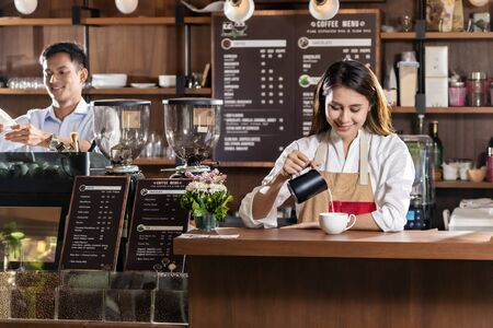 Young adult asian female barista pouring fresh milk to prepare latte coffee for customer in cafe bar. Banque d'images - 138288609