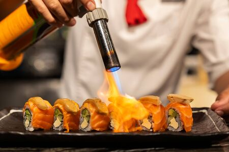 Koch kocht Lachs Foie Gras Roll, Fusion japanische Küche Essen, mit Gasbrenner Fackel.