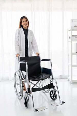 Portrait of confident female doctor medical professional holding wheelchair examination room in hospital clinic 스톡 콘텐츠