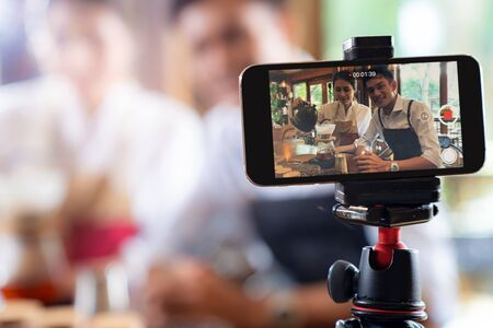 VLOG del empresario propietario asiático adulto joven revisa la cafetería y vive en las redes sociales para el marketing en línea con el teléfono inteligente en la cafetería. Utilizando para la puesta en marcha del concepto de consumo y fabricación de pequeñas empresas.