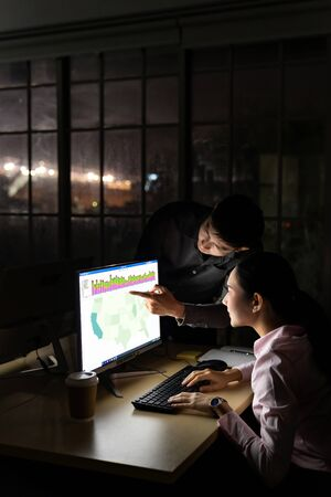 Young adult asian businessman dicuss with collegue about work late at night in their office with desktop computer. Using as hard working and working late concept.