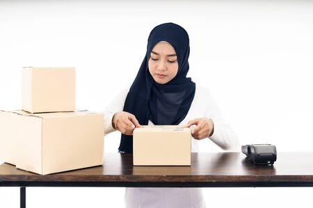Asian muslim women merchant working with laptop computer from home on wooden table with postal parcel cardboard boxes preparing for shipping her order. Studio shot on white background using as Selling online and small business SME ideas concept